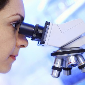 Scientist researcher looking into a microscope.