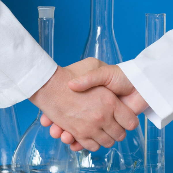 Handshake in Front of Beakers